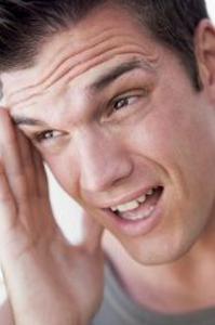 Ein Mann hat Kopfschmerzen, da er falsch atmet. Er fast sich an die Schläfe