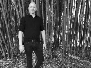 Volker Schmitz steht vor einem Bambushain in Schwarzweiss