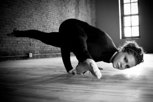 Frau macht eine Balance Stellung auf den Armen mit einem Bein nach vorne gestreckt