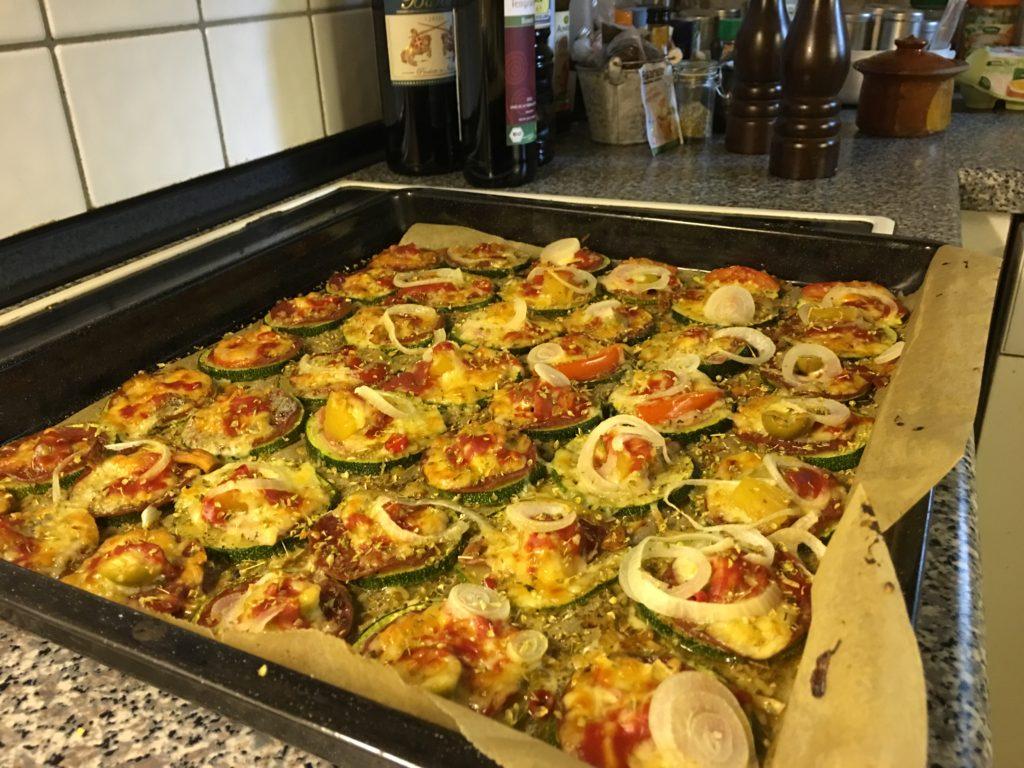 Pizza auf Zucchini, mit Oliven, Ziegenkäse, Gouda, Zwiebeln, Knoblauch Oregano und passierten Tomaten
