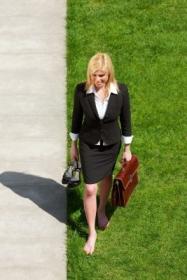 Frau erdet sich durch barfuß Gehen im feuchten Gras